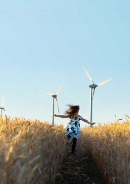 Girl running in a field with wind turbines in the background